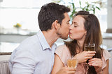 Loving couple with wine glasses kissing