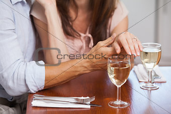 Mid section of woman showing engagement ring with wine glasses on table