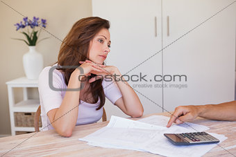 Angry young woman with hand pointing at home bills