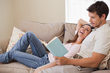 Relaxed couple reading book on couch