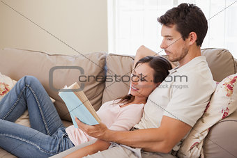 Relaxed young couple reading book on couch