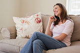 Smiling woman using mobile phone in living room
