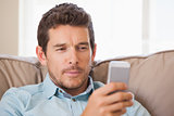 Young man text messaging in living room