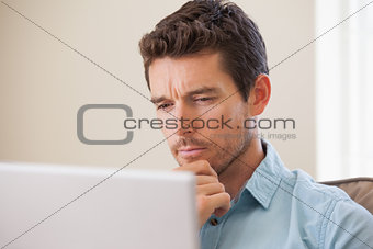 Concentrated man using laptop in living room