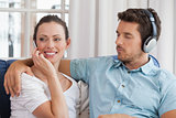 Couple with mobile phone and headphones in living room