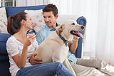 Couple with wine glass and pet dog in living room
