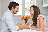 Loving young couple holding hands in kitchen