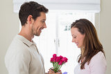 Man giving happy woman flowers at home