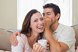 Man whispering secret into a cheerful womans ear in living room