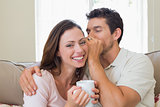 Man whispering secret into a womans ear in living room