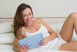 Portrait of a smiling woman using digital tablet in bed