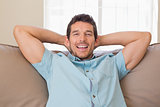 Portrait of happy relaxed man sitting on couch