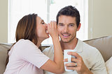 Woman whispering secret into a happy mans ear in living room