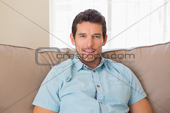 Portrait of content relaxed man sitting on couch