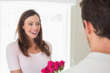 Cheerful woman looking at man with flowers