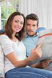 Relaxed young couple reading newspaper on couch