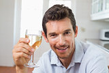 Smiling man holding a wine glass at home
