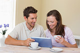 Couple using digital tablet while having coffee