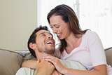 Close-up of cheerful loving couple sitting on couch