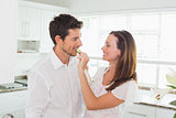 Loving woman feeding man cucumber slice in kitchen