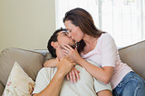 Loving relaxed couple kissing in living room