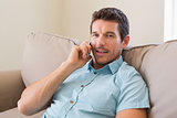 Smiling man using mobile phone in living room