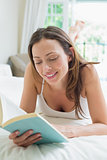 Relaxed young woman reading a book in bed