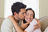 Loving young man kissing woman at home