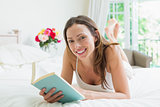 Relaxed smiling woman reading a book in bed