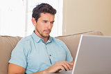 Concentrated young man using laptop on couch