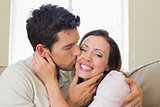 Loving young man kissing woman in living room