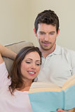 Loving relaxed couple reading book on couch