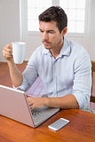 Man drinking coffee and using laptop at home