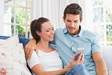 Smiling couple text messaging in living room