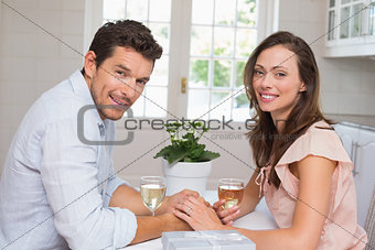 Portrait of smiling couple with wine glasses at home