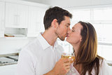 Loving couple kissing with wine glass in hand in kitchen
