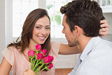 Happy woman and man with flowers at home