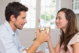 Loving couple toasting wine glasses at home