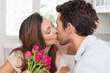 Loving couple kissing with flowers in hand at home