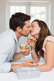 Loving young couple kissing with wine glasses