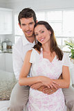 Loving man embracing woman from behind in kitchen