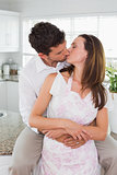 Loving young couple kissing in kitchen