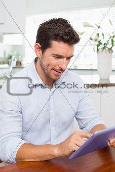 Concentrated relaxed man using digital tablet in kitchen