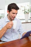 Man using digital tablet while having coffee at home