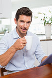 Smiling man using digital tablet while having coffeeat home