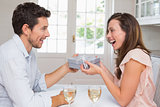 Man giving happy woman a gift box at home