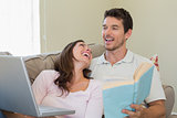 Cheerful couple with laptop and book at home