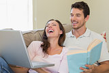 Cheerful couple with laptop and book sitting on couch