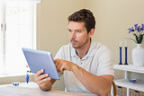 Concentrated man using digital tablet on table