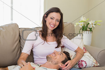 Happy man resting on womans lap on couch